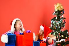 Girls celebrate New Year, copy space. Partying and holiday concept. Children with smiling faces sit on red background. Sisters in Santa hats with gift boxes stock photography