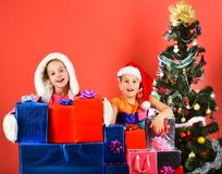 Girls celebrate New Year. Partying and holiday concept. Children with joyful faces sit on red background. Sisters in Santa Claus hats with gift boxes and royalty free stock photo