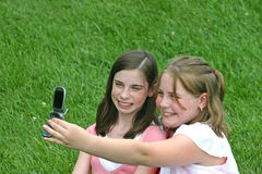 Girls on Cell Phones. Girl taking pictures on cell phone Royalty Free Stock Image