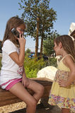 Girls and cellphone. Two young girls, the younger waiting for her older sister to get off her cellphone Royalty Free Stock Image
