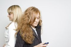 Girls / cellphone / problems. Two girls in business attire standing back to back while one looks at her cellphone Stock Photography