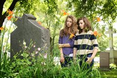 Girls at the cemetery. Two girls praying in front of a tomb in a cemetery Stock Photo