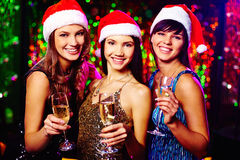 Girls with champagne. Three cheerful girls in Santa caps toasting at Christmas party stock photography