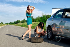Girls changing a tire. Stock Photo