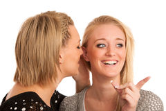 Girls chat - woman whispers on friends ear Stock Images