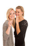 Girls chat - woman whispers on friends ear Stock Photography
