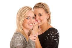 Girls chat - woman whispers on friends ear Royalty Free Stock Photography