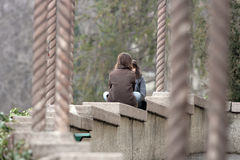Girls chating. Two girls siting on the wall Royalty Free Stock Photography