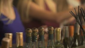 Girls chatting online using smartphones, wine bottles at nightclub bar counter. Stock footage stock video footage