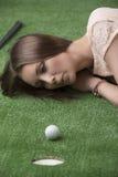 Girlâs che si trova sull'erba con la sfera di golf Fotografia Stock