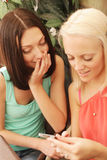 Girls checking out their new mobilephone at home Royalty Free Stock Image