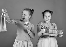 Girls with cheerful faces pose with candies and presents on green background. Sisters with lollipops, boxes and bags. Children eat big colorful sweet caramels stock photo