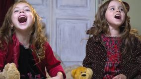 Girls cheerfully scream and play with plush toys stock video footage