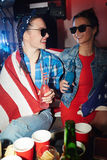 Girls cheering. Two American cheering girls with bottles of drinks enjoying party stock photography