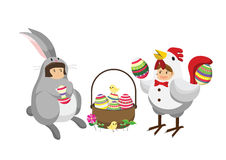 Girls in chicken costume and bunny rabbit costume with a basket full of decorated Easter eggs. Stock Photos