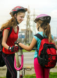 Girls children cycling pump up bicycle tire. Stock Image