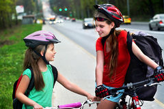Girls children cycling on yellow bike lane. There are cars on road. Stock Photography