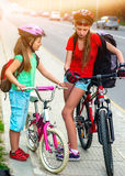 Girls children cycling on yellow bike lane. There are cars on road. Royalty Free Stock Images