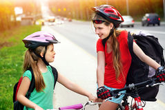 Girls children cycling on yellow bike lane. There are cars on road. Bikes bicyclist girl. Girls wearing bicycle helmet and glass with rucksack ciclyng bicycle Stock Photography