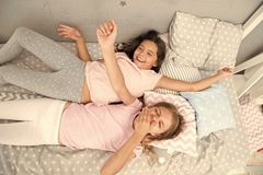 Girls children lay on bed with cute pillows top view. Pajamas party concept. Girls have fun. Girlish secrets honest and. Sincere. Friends cheerful playful mood stock image
