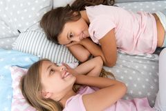 Girls children lay on bed with cute pillows top view. Pajamas party concept. Girls having fun. Girlish secrets honest. And sincere. Friends trust and feel stock image