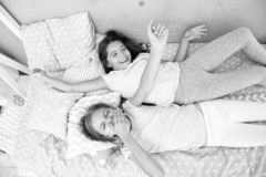 Girls children lay on bed with cute pillows top view. Pajamas party concept. Girls have fun. Girlish secrets honest and. Sincere. Friends cheerful playful mood stock images