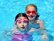 Girls children pool. Two girls having fun in a swimming pool Stock Image