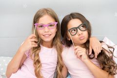 Girls children posing with grimaces photo booth props. Pajamas party concept. Girls friends having fun pajamas party. Friends cheerful posing with eyeglasses royalty free stock photography