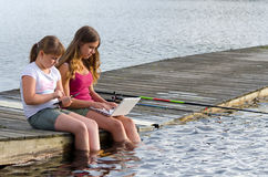 Girls choose social media instead fishing Royalty Free Stock Images