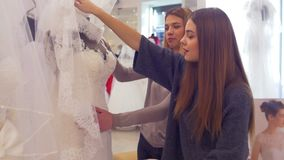 Girls choose a wedding dress. Woman in wedding salon. A friend helps to choose a dress stock video footage