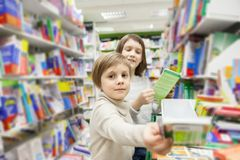 Girls choosing books in bookstore for school. Portrait of girls of 8 and 6 years in shop choosing books stock photos