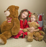 Girls With Christmas and Bears Presents. Two sisters with curls in their hair and dressed in red velvet dresses with matching red bows in their hair, sit next to Royalty Free Stock Images
