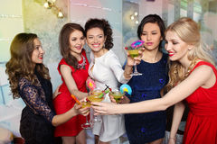 Girls clinking glasses of cocktails at the party Stock Image