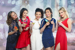 Girls clinking glasses of cocktails at the party Royalty Free Stock Photos