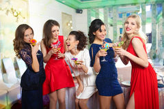 Girls clinking glasses of cocktails at the party Royalty Free Stock Photo