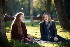 Girls in coats communicate sitting on a plaid in autumn park royalty free stock photos