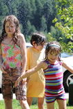 Elementary aged girls in a cold sprinkler Stock Image