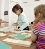 Girls   collecting   wooden puzzle Stock Images