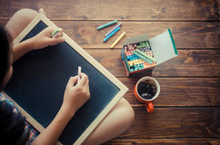 Girls are colored chalk to write on the black board.  Royalty Free Stock Images