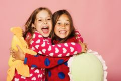 Girls in colorful polka dotted pajamas hold funny bright pillows. Children with happy faces and loose hair hug. Kids in bright clothes on pink background royalty free stock photo