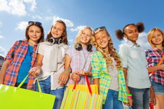 Girls with colorful shopping bags stand arm-in-arm royalty free stock photos