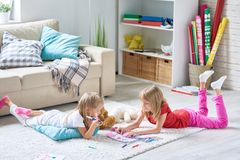 Girls Coloring Pictures on Floor. Portrait of cute little sisters coloring pictures together lying on floor on thick plush carpet in cozy living room at home Royalty Free Stock Photos