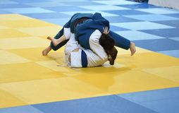 Girls compete in Judo. Two Girls judoka in kimono compete on the tatami Stock Images