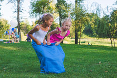 Girls compete in a relay race . Jumping in bags . They laugh and fall . Royalty Free Stock Images
