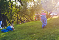 Girls compete in a relay race . Jumping in bags . They laugh and fall . Royalty Free Stock Photos