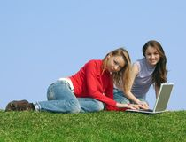 Girls and a computer. Two attractive girls with a computer, sitting on a green grass on a background of the blue sky Stock Photo