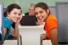 Girls computer class. Cute high school girls in computer class looking back Stock Photo