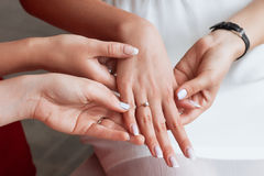 Girls consider the bride's ring. Groom's hand putting a wedding ring on the bride's finger stock image