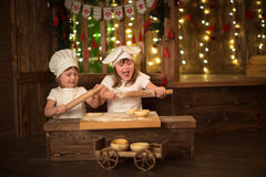 Girls cook with a rolling pin to stretch dough, the concept of c Stock Photo