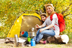 Girls cook soup in metallic pot sitting near tent Stock Image
